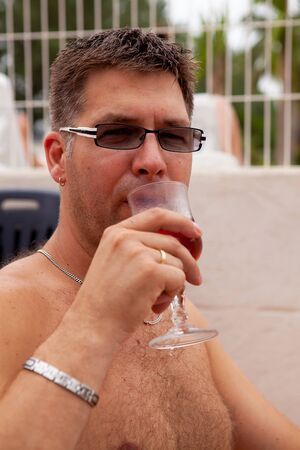 Relaxation; man is drinking rosé wine on vacation photo