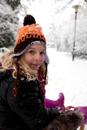 looking into camera: Ragazza sulla slitta nella neve guardando la telecamera Archivio Fotografico