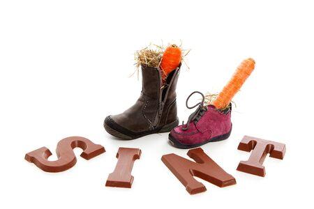 Sinterklaas, typisch Nederlands evenement met chocolade letters en wortel in de schoenen op een witte achtergrond