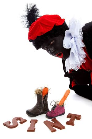 sinterklaas: Sinterklaas, typisch holl�ndische Veranstaltung mit Zwarte Piet (black pete) chocolate letters und Karotten in Schuhen auf wei�em Hintergrund