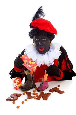 Sinterklaas, typisch Nederlands evenement met Zwarte Piet (Zwarte Piet) chocolade letters en wortel in de schoenen op een witte achtergrond
