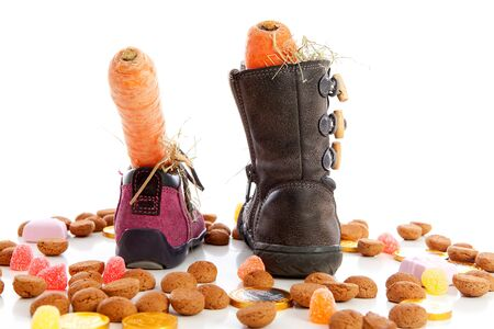 strooigoed: Sinterklaas, typical Dutch event with pepernoten and carrot in shoes over white background