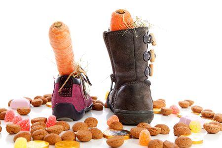 Sinterklaas, typisch Nederlands evenement met pepernoten en wortel in de schoenen op een witte achtergrond Stockfoto
