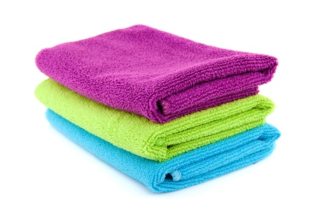 stacked colorful folded towels over white background Standard-Bild