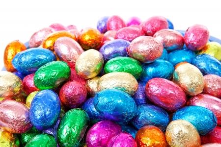 oeufs en chocolat: Pile d'oeufs de P�ques color�s en gros plan sur fond blanc Banque d'images