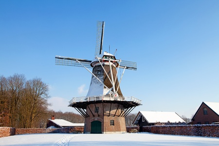 Dutch windmill near Apple farm in the snow photo