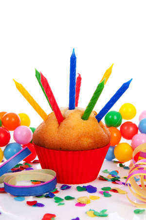 Birthday cupcake with lots of candles, party streamers and colorful confetti over white background photo