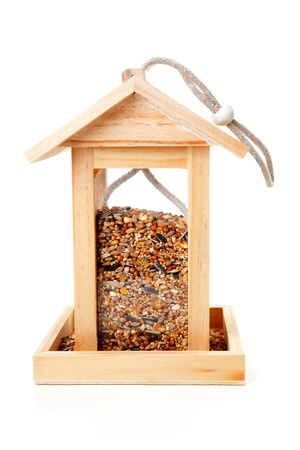 wooden bird feeder house with food over white background