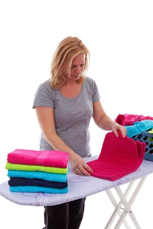 Housewife is folding colorful towels over white background photo