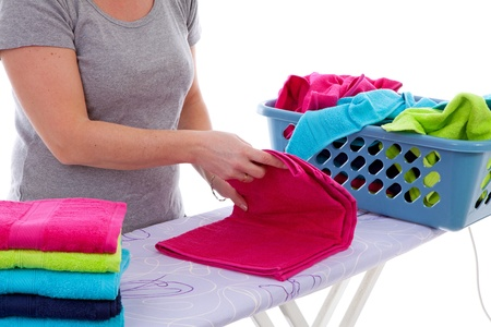 Housewife is folding colorful towels in closeup over white background