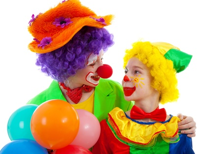 two children dressed as colorful funny clown with balloons over white background Stock Photo