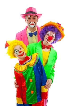 Three people dressed up as colorful funny clowns over white background photo