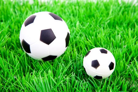 One big and one little soccer ball on plastic grass  photo