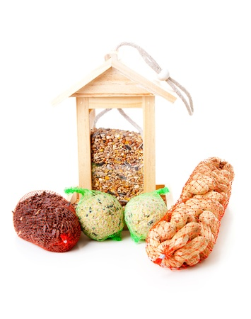 bird house: wooden bird feeder house with food over white background