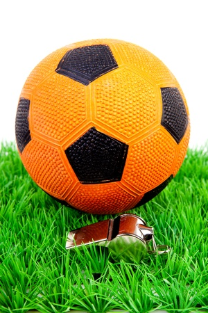 Orange soccer ball and flute on grass over white background photo