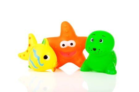 Colorful rubber bath toys over white background photo