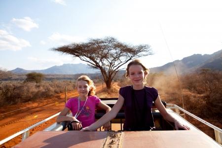 Going on safari zwei Mädchen stehen an der Spitze der Jeep