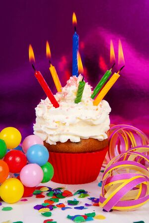 Birthday cupcake with lots of candles, party streamers and colorful confetti over purple background photo