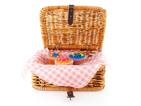 picknick: Picnic basket with decorated cupcakes over white background