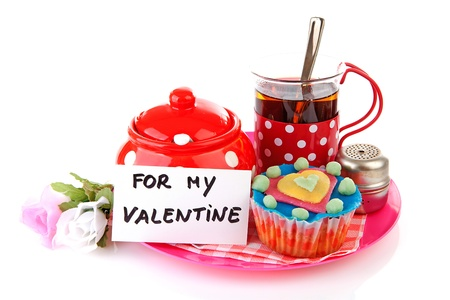 breakfast for my Valentine; cup of tea and cupcake over white background photo