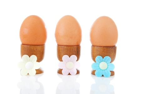Three chicken eggs in a row in wooden holders over white background photo