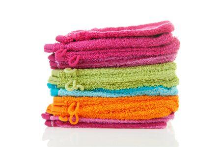 orange washcloth: Pile of colorful washclothes over white background