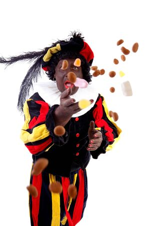 strooigoed: Zwarte piet ( black pete) typical Dutch character part of a traditional event celebrating the birthday of Sinterklaas in december over white background throwing pepernoten ( ginger nuts)  Stock Photo