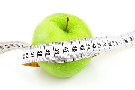 Fresh green apple with measure tape over white background photo