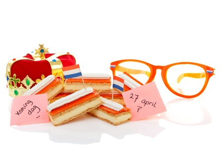 Typical Dutch tompouce sweet with crown and orange glasses over white background