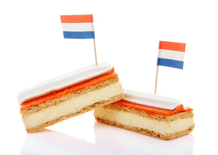 Two traditional Dutch pastry called tompouce  with flags over white background Standard-Bild