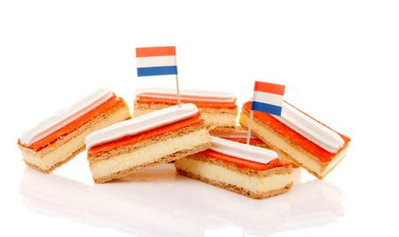 Pile of traditional Dutch pastry called tompouce with flags over white background photo