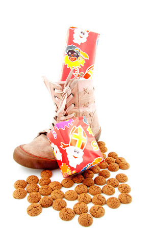 strooigoed: Ginger nuts and gifts in shoe for Dutch event in december over white background
