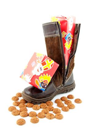 Pepernoten en cadeaus in laars voor Nederlands evenement in december over witte achtergrond Stockfoto - 23198857