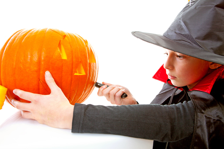 Girl is cutting pumpkin face for Halloween over white background photo