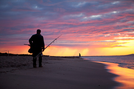 silhouette of fisherman by the ocean in sunrise photo
