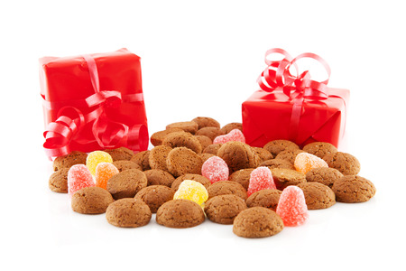 ginger nuts: Typical dutch sweets: pepernoten (ginger nuts) and red presents for celebration at 5 december in the Netherlands over white background