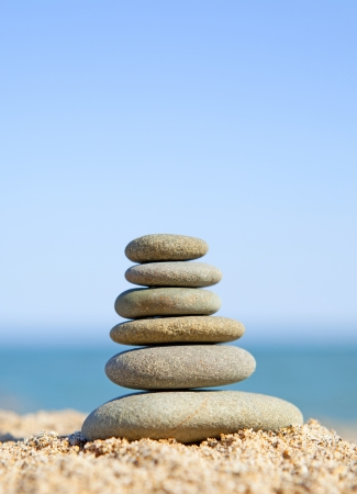 stack of zen stones near the ocean on sunny day photo