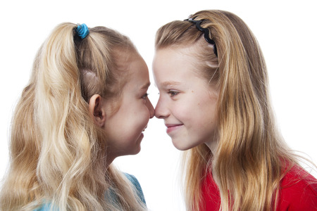 Two sisters nose to nose over white background photo