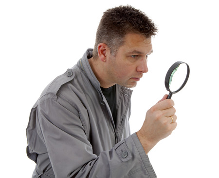 Man with raincoat is looking with magnifying glass over white background photo