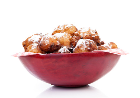 Bowl with Pile of Dutch donut also known as oliebollen, traditional New Years eve food isolated on white background Stock Photo