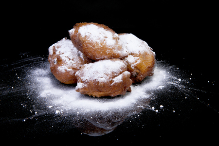 Pile of Dutch donut also known as oliebollen, traditional New Years eve food isolated over black background  photo