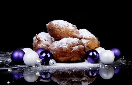 Pile of Dutch donut also known as oliebollen, traditional New Years eve food isolated over black background and Christmas balls