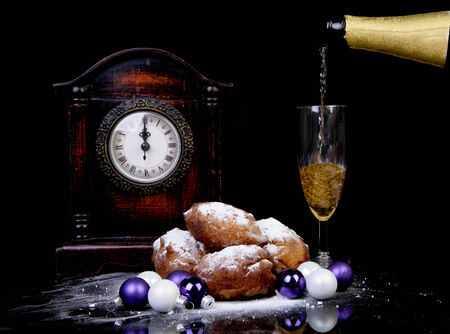 Dutch donut also known as oliebollen, traditional New Years eve food, clock on midnight and champagne over black background Stock Photo