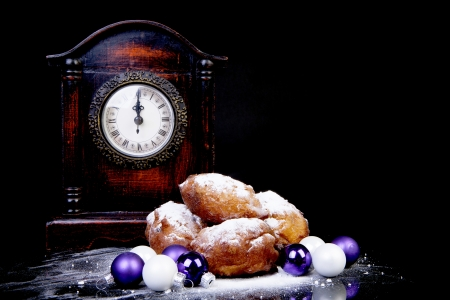 Dutch donut also known as oliebollen, traditional New Years eve food, clock on midnight over black background