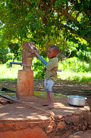KINAZINI, KENYA - JULY-12: unidentified African boy is showing a water well for tourists with traditional welcome on July 12, 2011 in a local village in Kinazini, Kenya