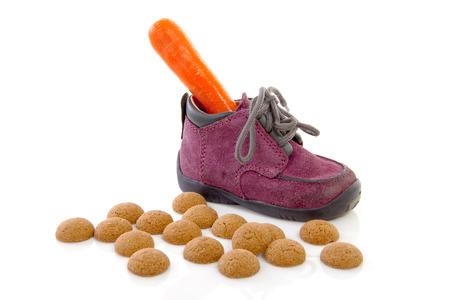 De paarse kleine kinderen schoen met wortel en pepernoten (gember nuts), traditioneel voor Sinterklaas in Nederland op witte achtergrond Stockfoto