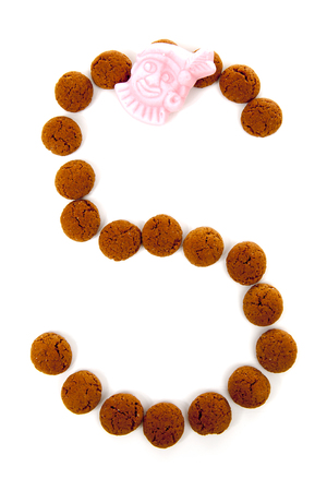 pepernoten: Ginger nuts, pepernoten, in the shape of letter S isolated on white background. Typical Dutch candy for Sinterklaas event in december