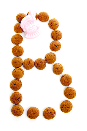 dutch typical: Ginger nuts, pepernoten, in the shape of letter B isolated on white background. Typical Dutch candy for Sinterklaas event in december