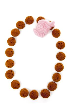ginger nuts: Ginger nuts, pepernoten, in the shape of letter O isolated on white background. Typical Dutch candy for Sinterklaas event in december Stock Photo