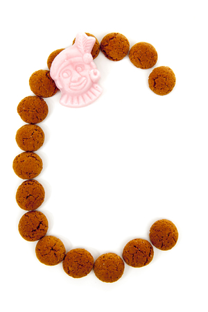 sinterklaas: Ginger nuts, pepernoten, in the shape of letter C isolated on white background. Typical Dutch candy for Sinterklaas event in december